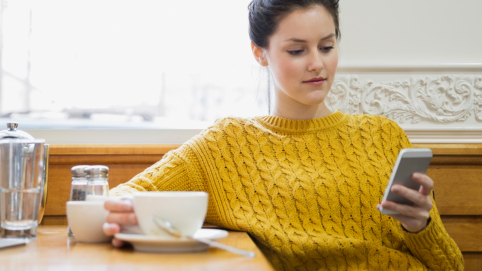 A woman sitting in a cafe holding a cup in right hand and viewing a mobile phone held in her left hand.